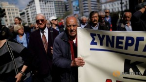 greek-pensioner-holds-banner-during-demonstration-against