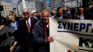 greek-pensioner-holds-banner-during-demonstration-against